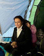 France. Refugees. Grande Synthe camp near Dunkirk/Dunkerque.People are camping in a wood with very few facilities. A mother from Iraq with one of her children