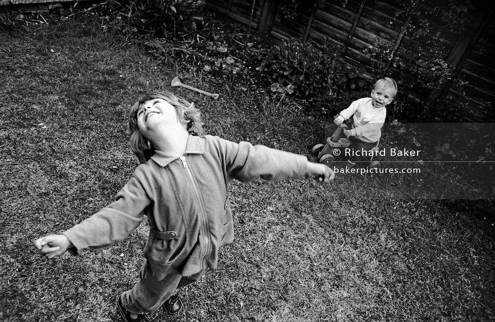 """A three year-old girl throws her head back with joy while playing with her young one-year-old brother in the back garden of their South London home. We look down on the small girl who throws her head back with delight and the freedom of an early summer afternoon at home. Little brother laughs with pleasure too, sitting on a toy tractor. The picture is slanted to lend a sense of drama. From a personal documentary project entitled """"Next of Kin"""" about the photographer's two children's early years spent in parallel universes. Model released."""
