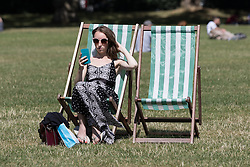 © Licensed to London News Pictures. 12/08/2016. LONDON, UK.  A woman takes a selfie as she sunbathes during the hot and sunny weather today in Green Park in London this lunchtime.  Photo credit: Vickie Flores/LNP
