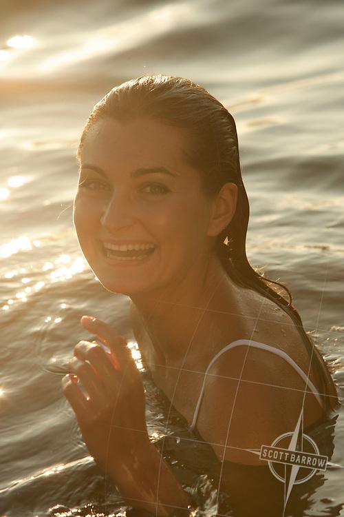 Young woman swimming in lake.