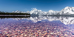 Colorful rocks of the bottom of Jackson Lake in Grand Teton National Park, The Grand Teton reflection upon the placid water beyond.