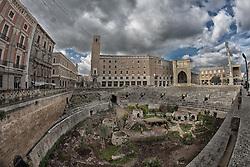 L'anfiteatro romano, insieme al teatro, è il monumento più espressivo dell'importanza raggiunta da Lupiae, l'antenata romana di Lecce, tra il I e il II secolo d.C. La datazione del monumento è ancora oggetto di discussione e oscilla tra l'età augustea e quella traiano-adrianea. L'anfiteatro misurava all'esterno 102 x 83 m, con l'arena di 53 x 34 m, e poteva contenere circa 25.000 spettatori. Il monumento venne scoperto durante i lavori di costruzione del palazzo della Banca d'Italia, effettuati nei primi anni del '900. Le operazioni di scavo per riportare alla luce i resti dell'anfiteatro iniziarono quasi subito, grazie alla volontà dell'archeologo salentino Cosimo De Giorgi e si protrassero sino al 1940..Attualmente è possibile ammirare solo un terzo dell'intera struttura, in quanto il resto rimane ancora nascosto nel sottosuolo di piazza Sant'Oronzo dove si ergono alcuni edifici e la chiesa di Santa Maria della Grazia.