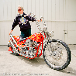 Arlen hides his broken leg behind his Red Flamed Shovelhead. (He broke it while out on a trail ride with Cycle World Magazine.) San Leandro, CA. Photograph ©Michael Lichter 1994