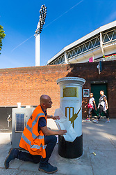 Tony Newlin for Royal Mail applies the vinyl decals as Royal Mail unveils a white-painted postbox outside Lords Cricket Ground with a plaque and graphics that celebrate England's ICC Cricket World Cup Victory. London, July 16 2019.