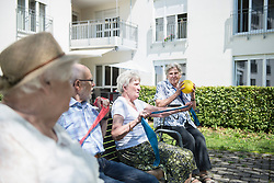 Senior women and man exercising with resistance band at rest home garden, Bavaria, Germany, Europe