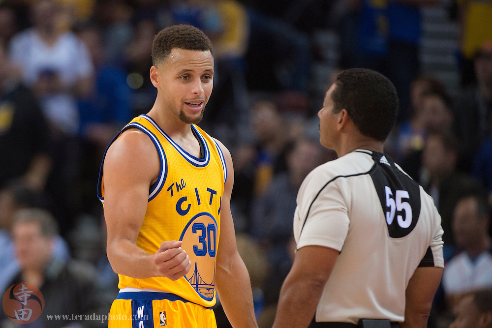 November 17, 2015; Oakland, CA, USA; Golden State Warriors guard Stephen Curry (30) argues with NBA referee Bill Kennedy (55) during the third quarter against the Toronto Raptors at Oracle Arena. The Warriors defeated the Raptors 115-110.