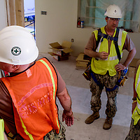 Alfredo Estrella, right, Trip Woolf and other members of the Navy Construction Battalion work on the final fittings for a home at the Southwest Indian Foundation in Gallup July 26.