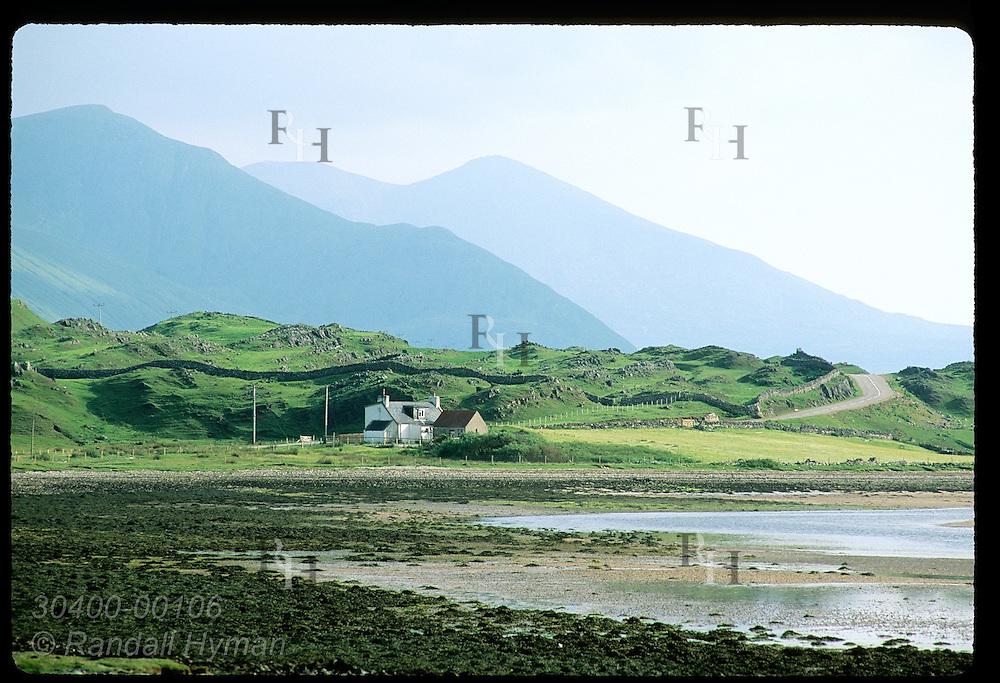Farmhouse huddles below imposing mountains along west coast of Scotland; Kyle of Durness. Scotland