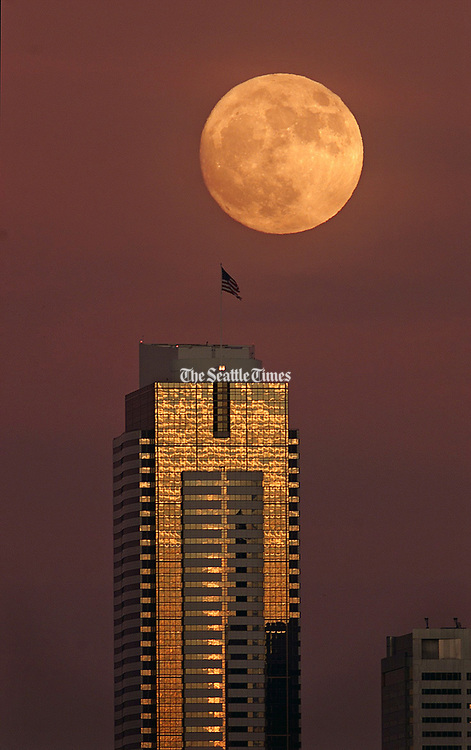 In this 1999 photo, a bulbous moon rises over the Seattle skyline, a prelude to the full moon, which was 24 percent brighter than normal because it coincided with the winter solstice and the lunar perigee. (Steve Ringman / The Seattle Times)