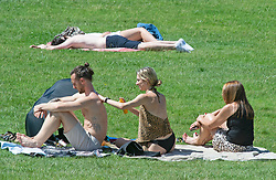 © Licensed to London News Pictures 08/06/2021. Greenwich, UK. People applying suncream in Greenwich Park, London while sunbathing and enjoying the hot sunny weather today. More hot sun is expected at the weekend with hotter temperatures across the UK. Photo credit:Grant Falvey/LNP