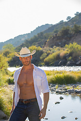 cowboy with an open shirt by a river
