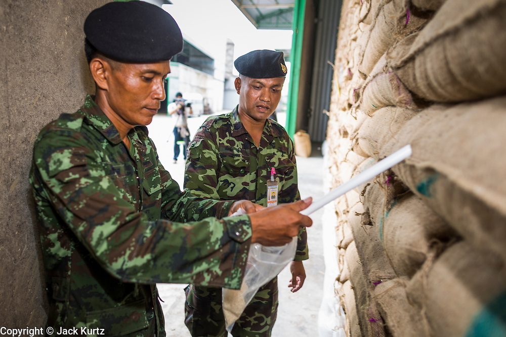 """08 JULY 2014 - WANG NAM SAP, SUPHAN BURI, THAILAND: Thai soldiers draw samples of rice from burlap bags at a rice warehouse in Wang Nam Sap, Suphan Buri province. Representatives of the Thai ruling junta have started inspecting stocks of rice bought by the ousted civilian government following the 2012 and 2013 rice harvests. The government of ousted former Prime Minister Yingluck Shinawatra bought up thousands of tons of rice from farmers at above market prices in one of its most controversial populist policies. The alleged mismanagement of the """"rice pledging scheme,"""" as it was called, was one of the factors that lead to the May 2014 coup that ousted the government. According to officials doing the inspections found rotten and weevil-infested grain, along with evidence that large stocks were replaced with old or inferior grades.     PHOTO BY JACK KURTZ"""