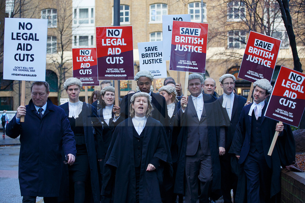 © licensed to London News Pictures. London, UK 06/01/2014. Lawyers protesting against the legal aid cuts outside Southwark Crown Court in London on Monday, 6 January 2013. Across England and Wales barristers and solicitors stage an unprecedented mass walkout in protest at government plans to slash legal aid fees by up to 30%. Photo credit: Tolga Akmen/LNP