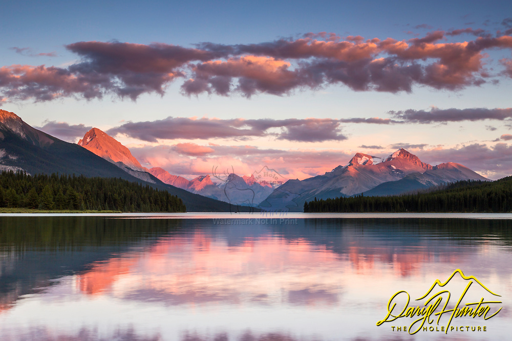 Sunset at Maligne Lake in the heart of Jasper National Park, the Queen Elizebeth Range reflecting upon the calm waters of the lake.