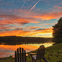 Massachusetts sunset photography with lawn chairs providing front row seating to a Mother Nature spectacle at Lake Waban in Wellesley Massachusetts. This Massachusetts lake with Wellesley College nearby are inspiring and make for a beautiful New England nature photography location to visit and to get lost with a camera.<br />