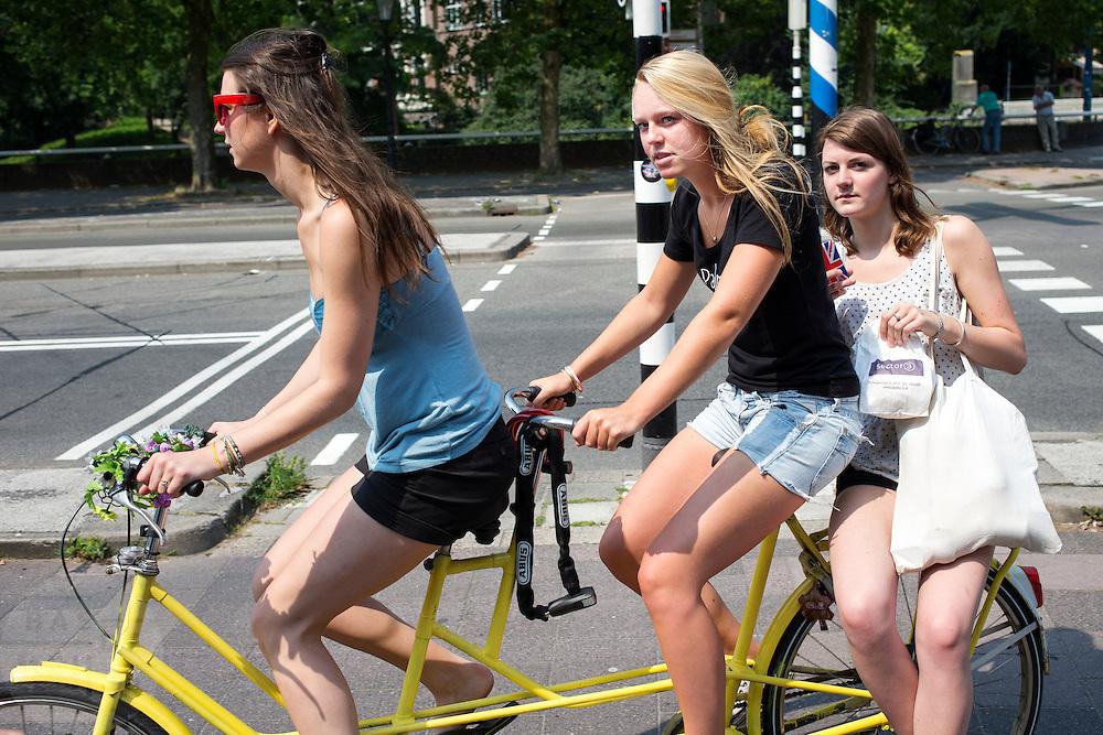 Drie meisjes fietsen op een tandem door Utrecht.<br /> <br /> Three girls are riding on a tandem.