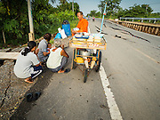 14 JULY 2015 - THAILAND: A Buddhist monk prays with women who presented him with food and alms on damaged road in Pathum Thani province. The road bed collapsed because of subsidence. The drought that has crippled agriculture in central Thailand is now impacting residential areas near Bangkok. The Thai government is reporting that more than 250,000 homes in the provinces surrounding Bangkok have had their domestic water cut because the canals that supply water to local treatment plants were too low to feed the plants. Local government agencies and the Thai army are trucking water to impacted communities and homes. Roads in the area have started collapsing because of subsidence caused by the retreating waters. Central Thailand is contending with drought. By one estimate, about 80 percent of Thailand's agricultural land is in drought like conditions and farmers have been told to stop planting new acreage of rice, the area's principal cash crop.       PHOTO BY JACK KURTZ