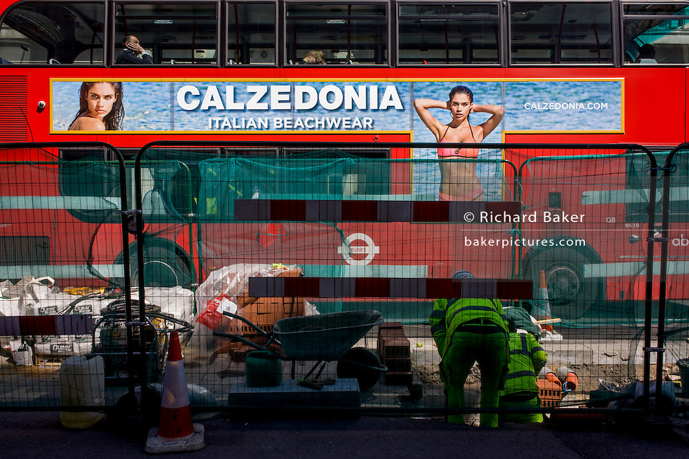 London bus with side advert for Italian swimwear label Calzedonia, stopped at lights by construction work in central London.