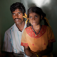 """Viswanathan with his daughter Vijyashree at home in the fishing village of Thazanguda, near Cuddalore. ..Vijita (age 14) and Vijyashree (age 11) Viswanathan lost their mother and brother to the tsunami in 2004. They continue to live in the fishing village of Thazanguda with their father Viswanathan, his second wife Kayalvizhi and their two children Sanjay (age 3) and Monica (age 1). ..Until the beginning of the 2009 academic year in June, Vijita and Vijyashree attended the local Thazanguda school. This village school teaches pupils only until the 8th Standard and with Vijita now entering the 9th, it was decided that the two daughters remain together and both travel 3km to the local town school: the Government Girls High School, Venugopalapuram in Cuddalore. ..At the same time Viswanathan decided he would cease day-to-day care of his daughters and place them in the Government Home for Tsunami Children, also in Cuddalore. This was not a move welcomed by either Vijita or Vijyashree and one afternoon after just two weeks at the orphanage, the two girls ran away. At roll call in the orphanage that evening the alarm was sounded and the two sisters were eventually located in Thazanguda waiting for their father and Kayalvizhi who were both away at the time. Realising his daughters' unhappiness, Viswanathan then took them out of the Government home. ..According to her class teacher, Vijita often compares her step-mother to her mother and concludes that she wants her mother back. Vijita confides in her teachers that her stepmother is forever demanding that she and her sister Vijyashree undertake housework. This frustration at home is tempered by the genuine love both sisters have for their father and two younger siblings Sanjay and Monica. Vijita expresses a lonelyness without her mother. Pushpavalli concludes that """"Vijita wants something else beyond the love of her father and sister"""". ..Viswanathan appears genuinely to want the best for his two elder daughters. His experimen"""