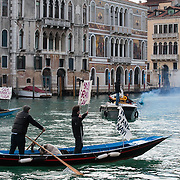 """VENICE, ITALY - JANUARY 16:  Protesters block the Grand Canal  while holding several banners reading """"Stop the large Ships""""  on the day of the special meeting discussing the environmental impact of cruises in St Mark's basin on January 16, 2012 in Venice, Italy. Protest are mounting in Venice against large cruise ships crossing St Marks's basin after the Costa Concordia tragedy.."""