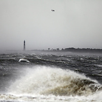 A rescue helicopter flies overhead as waves crash near Sullivan's Island in front of the Morris Island Lighthouse on Saturday as Hurricane Matthew moved away from the area. (ANDREW KNAPP/STAFF)