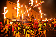 Lewes, UK. Monday 5th November 2012. Cliffe bonfire society members carry burning crosses. Bonfire Night celebration in the town of Lewes, East Sussex, UK which form the largest and most famous Guy Fawkes Night festivities. Held on 5 November, the event not only marks the date of the uncovering of the Gunpowder Treason and Plot in 1605, but also commemorates the memory of the 17 Protestant martyrs from the town burnt at the stake for their faith during the Marian Persecutions of 1555–57. There are six bonfire societies putting on parades involving some 3,000 people.