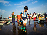 27 OCTOBER 2015 - YANGON, MYANMAR: Men unload fishing trawlers at a pier in the market at Aungmingalar Jetty in Yangon. The market is home to one of the largest fish markets in Yangon and a meat and produce market.    PHOTO BY JACK KURTZ