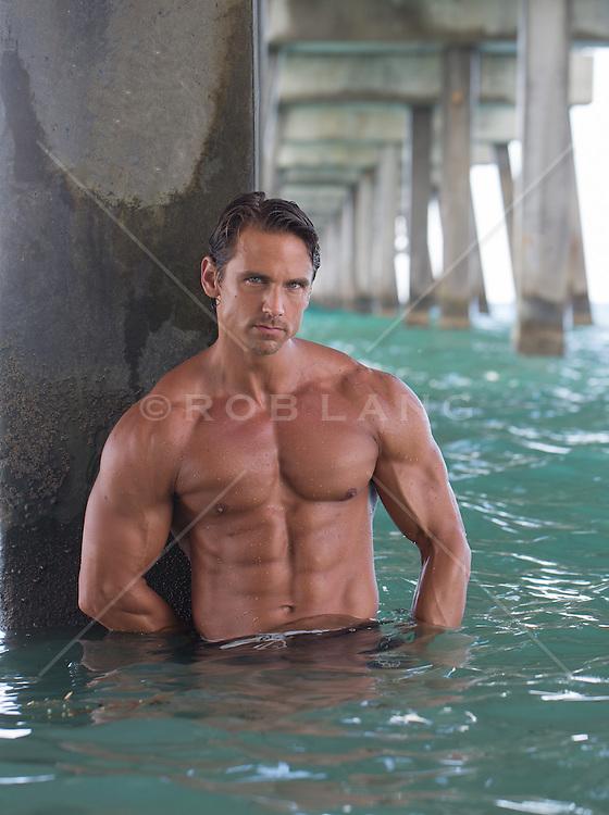 shirtless muscular man under the Dana Beach Pier in Florida