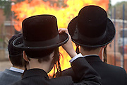 Orthodox Jewish schoolboys from the Bobov School watch their Lag B'Omer bonfire in the school playground. Lag B'Omer is the holiday celebrating the thirty-third day of the (counting of the) Omer. Jews celebrate it as the day when the plague that killed 24,000 people ended in the holy land (according to the Babylonian Talmud). Other sources say the plague was actually the Roman occupation and the 24,000 people died in the second Jewish - Roman war  (Bar Kokhba revolt of the first century).  Bonfires (used as signals in wartime) are symbolically lit to commemorate the holiday of Lag'B'Omer.
