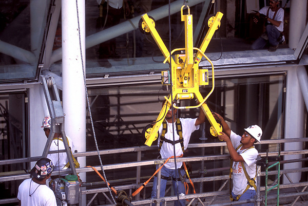 Stock photo of workmen maneuvering a device used for installation of glazing panels during new construction at the George R. Brown Convention Center in Houston, Texas