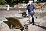 Farmer using large metal wheelbarrow to mcarry coffee in farmyard, Fazenda Sant' Anna, Campinas, Brazil, South America 1962