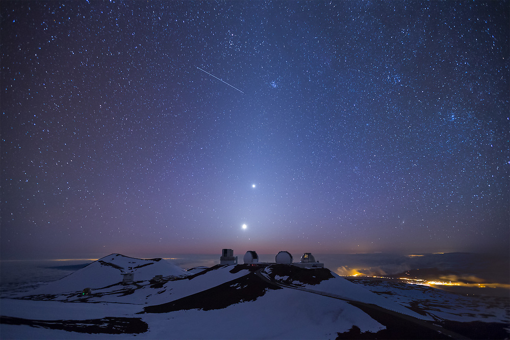 The view from the summit of Mauna Kea as the moon and Venus set over the western horizon. Visible in the image are the lights across the state...Waimea and Kawaihae in the lower right, Wailuku and Lahaina on the slopes of Haleakala's silhouette, a faint glow from Honolulu on the horizon to the left of Maui, and the glow from Kailua-Kona surrounding the pu'u, or cinder cone, on the left of the frame. The four prominent observatories from left to right are, the Subaru, the Keck twins, and the NASA IRIF. And lastly, that's a satellite streaking through the sky. So blessed to have a view like this in our backyard! Mahalo Ke Akua!!!