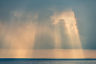 Sunbeams through dark clouds in the morning over the coast near Lehuawehi Point, South Hilo District, The Big Island of Hawai'i, Hawaii