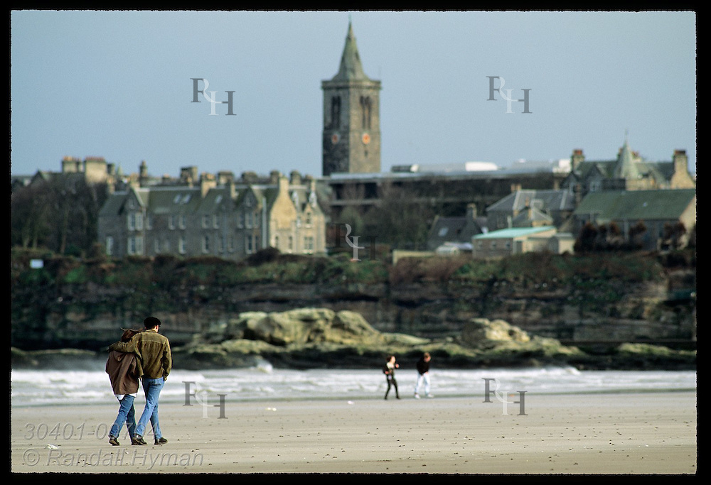 Young couple walks along beach opposite rocky cliffs and stone buildings of town of St Andrews. Scotland