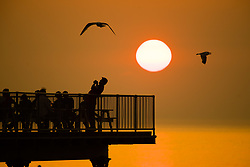 © Licensed to London News Pictures. 29/05/2018. Aberystwyth, UK. After yet another day of hot  sunny weather, the people on the pier in Aberystwyth on the west coast  of Wales are treated to a spectacular sunset over the sea. Photo credit: Keith Morris/LNP