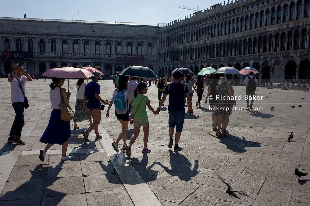 Tour group follow their guide in Piazza San Marco, Venice, Italy