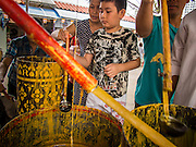 "21 JULY 2013 - BANGKOK, THAILAND:  People pour molten wax into candle molds to make merit at Wat Mahabut on the first day of Vassa, the three-month annual retreat observed by Theravada monks and nuns. The candles are then presented to the temple. Now monks rely on electric lights, but traditionally the temples relied on candles provided by the community. On the first day of Vassa (or Buddhist Lent) many Buddhists visit their temples to ""make merit."" During Vassa, monks and nuns remain inside monasteries and temple grounds, devoting their time to intensive meditation and study. Laypeople support the monastic sangha by bringing food, candles and other offerings to temples. Laypeople also often observe Vassa by giving up something, such as smoking or eating meat. For this reason, westerners sometimes call Vassa the ""Buddhist Lent.""       PHOTO BY JACK KURTZ"