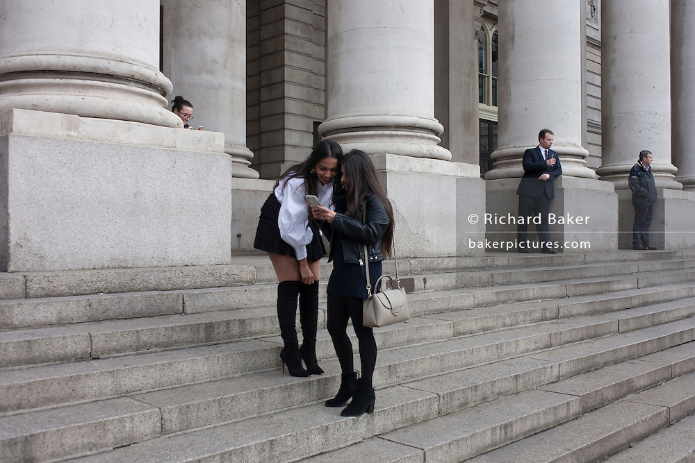 Two young women pause to admire their photos on the steps of Royal Exchange, on 9th December 2016, in the City of London.