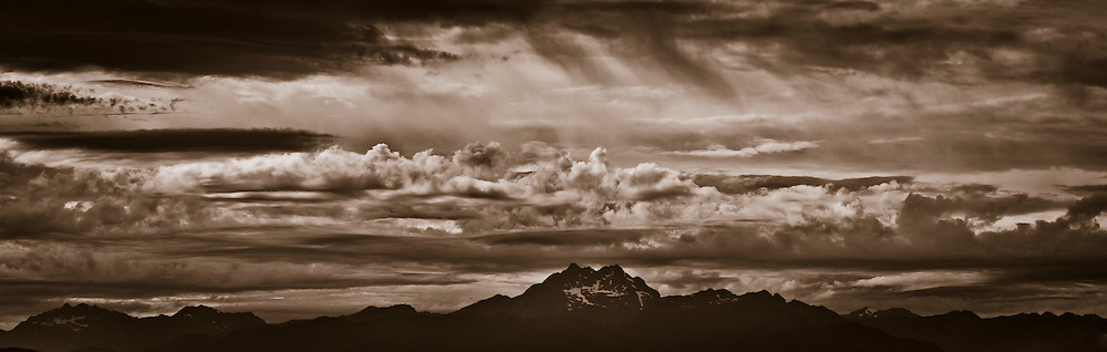 monochrome of clouds in unsettled air over The Brothers, a mountain of the Olympic Range seen from Puget Sound after sunset sepia