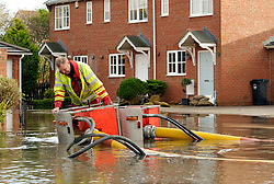 © Licensed to London News Pictures. 26/11/2012. Worle, Somerset, UK. Fire and rescue service use high capacity pumps to deal with flooding in Lanthony Close in Worle near Weston-super-Mare, Somerset.  Sofar the water has been kept out of local residents' houses.  25 November 2012..Photo credit : Simon Chapman/LNP