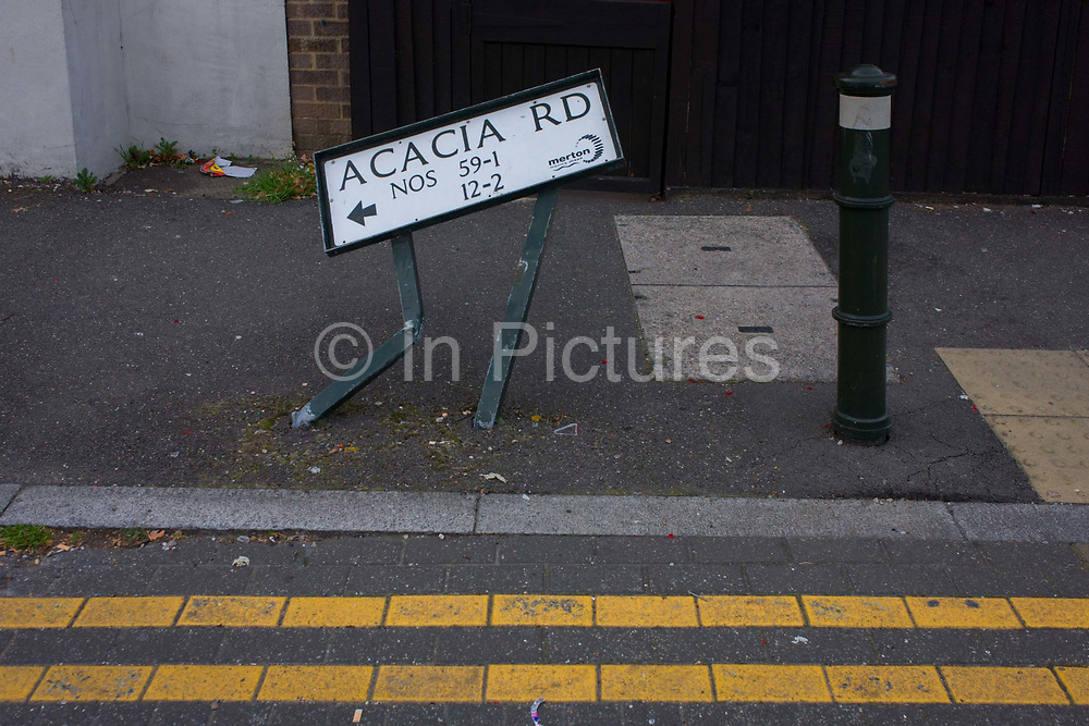 A bent street sign for Acacia Road in Mitcham, London borough of Merton. Apparently damaged by a reversing vehicle, in a side street of a south London estate, the sign is leaning as its human legs are bending at the knee, a curtsey or a bow. Acacia Road is also the generic name for an anywhere place, a location for the ordinary, average Britain. The borough of Merton is the result of a merger of Mitcham, Wimbledon and Merton & Morden Urban District, all formerly within Surrey. It has an area of 14.52 sq mi (37.61 km2) who ethnicity is 48.4% White British.