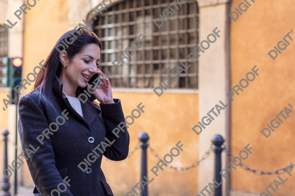 Young charming executive women talks by a mobile phone (cell phone) and smile while whole walking in Rome Italy