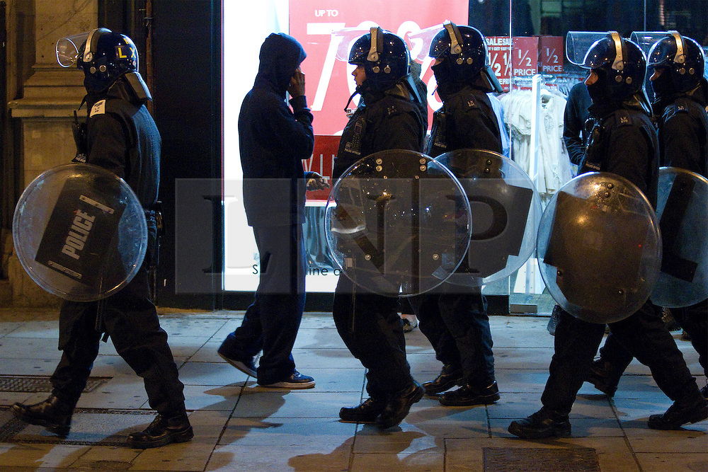 © Licensed to London News Pictures . FILE PICTURE DATED 09/08/2011. Camden , UK . A group of riot police walk in one direction on Camden High Street as a man with a hooded sweatshirt , talking on his mobile phone , walks by them in another , during a standoff between rioters and police after shops in Camden Town were smashed and looted . Following a first night of riots and looting in Tottenham , rioting and looting spreads to other areas . Photo credit : Joel Goodman/LNP