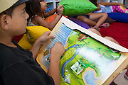 Bruno reading a pop up book in the community library, Biblioteca Comunitaria do Arquipelago, Porte Alegre, Brazil. <br /> <br /> Cirandar is working in partnership with  C&A and C&A Instituto to implement a network of Community Libraries in eight communities of Porto Alegre.
