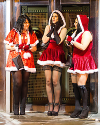 """© Licensed to London News Pictures . 15/12/2012 . Manchester , UK . Three women dressed in Santa Claus outfits take shelter in the lounge entrance of The Birdcage . Revellers enjoy a wet but busy night out on one of the last weekends before Christmas , a traditionally busy time when office parties and clubbers decent on bars and clubs , often known as """" Mad Friday """" . Photo credit : Joel Goodman/LNP"""