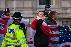 """London, February 8th 2015. Muslims demonstrate outside Downing Street  """"to denounce the uncivilised expressionists reprinting of the cartoon image of the Holy Prophet Muhammad"""". PICTURED: A far right anti-Islamic protester makes an insulting gesture at the thousands of Muslims attending the protest."""