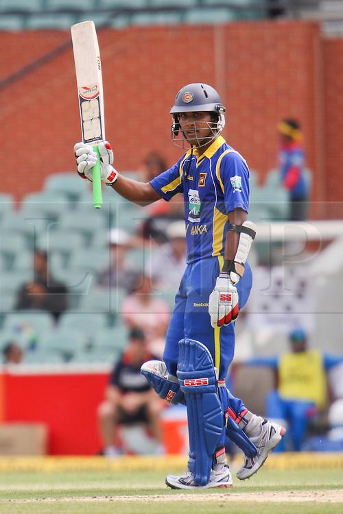© Licensed to London News Pictures. 14/02/2012. Adelaide Oval, Australia. Sri Lankan batsman Dinesh Chandimal raises his bat after making 50  during the One Day International cricket match between India Vs Sri Lanka. Photo credit : Asanka Brendon Ratnayake/LNP
