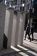 Two businessmen walk past modern pillar architecture in the City of London, the capital's financial district, on 21st October 2021, in London, England.
