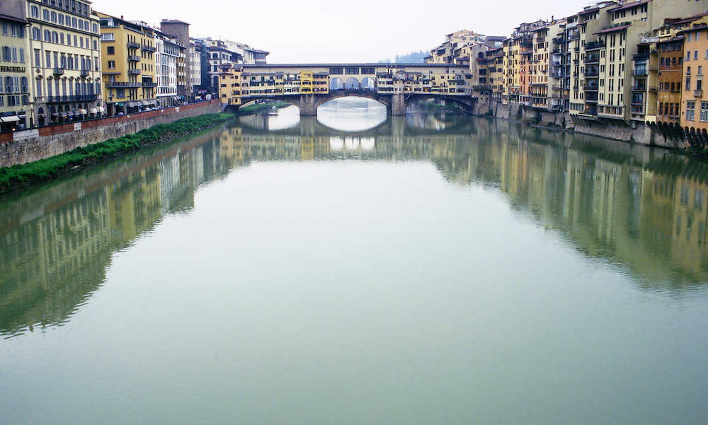 View of Ponte Vecchio Bridge and buildings lining Arno River in spring rain Florence Italy