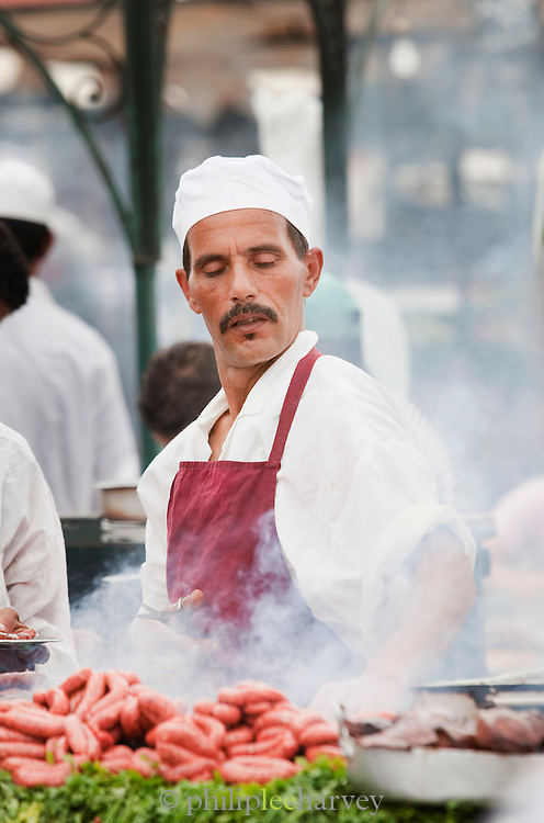 A chef cooks food at a stall in the Djemaa el Fna in the medina of Marrakech, Morocco. Every night the main square fills with dozens of food vendors and their carts.